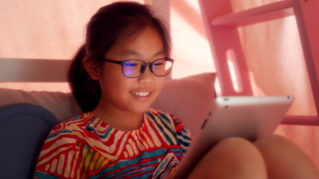 little girl using  digital table pc on bed - 8 9 anni video stock e b–roll
