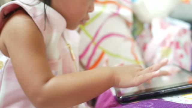 little girl using digital tablet video