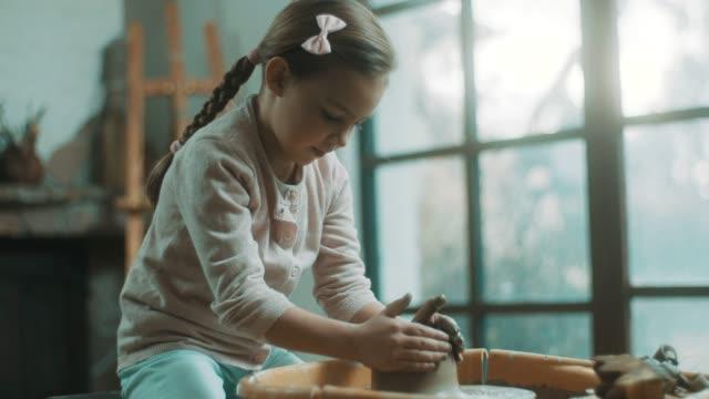 vídeos de stock, filmes e b-roll de menina usando a roda de oleiro no atelier - cerâmica artesanato