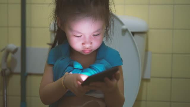 stockvideo's en b-roll-footage met meisje met behulp van slimme telefoon in toilet - cell phone toilet