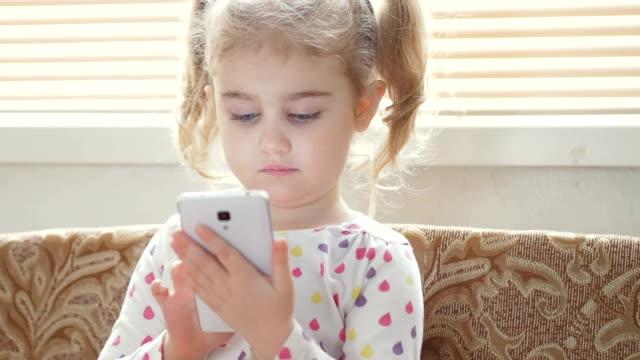 liten flicka med smartphone. barnet sitter nära fönstret. rum inomhus - digital reading child bildbanksvideor och videomaterial från bakom kulisserna