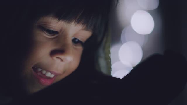 vidéos et rushes de petite fille à l'aide de tablette sous la couverture sur le lit - lumière noël