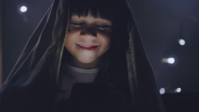 Little girl using tablet under the blanket on the bed video