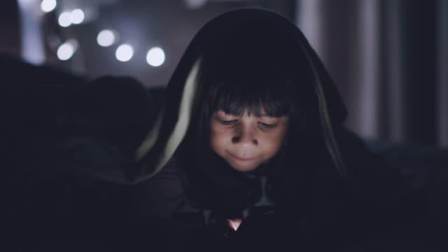 ベッドの上、毛布の下のタブレットを使用して小さな女の子 - スマホ ベッド点の映像素材/bロール
