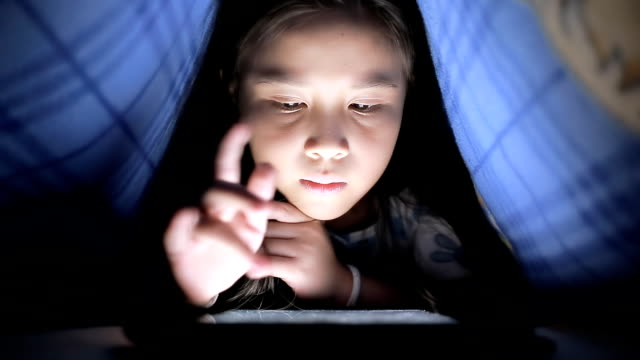 Little girl using tablet under the blanket