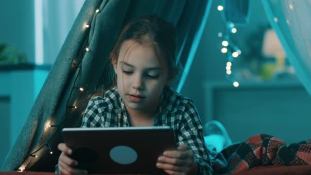 stockvideo's en b-roll-footage met meisje met behulp van tablet pc - een tablet gebruiken