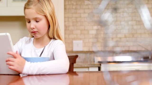 Little girl using tablet while having breakfast 4K 4k video