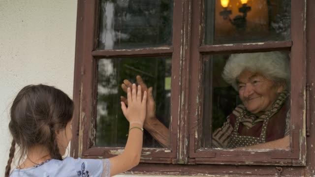 la bambina visita la nonna durante la pandemia attraverso la finestra - nipote femmina video stock e b–roll