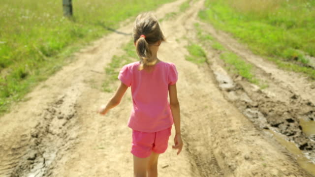 Little girl walking along a rural road Little girl walking along a rural road short length stock videos & royalty-free footage