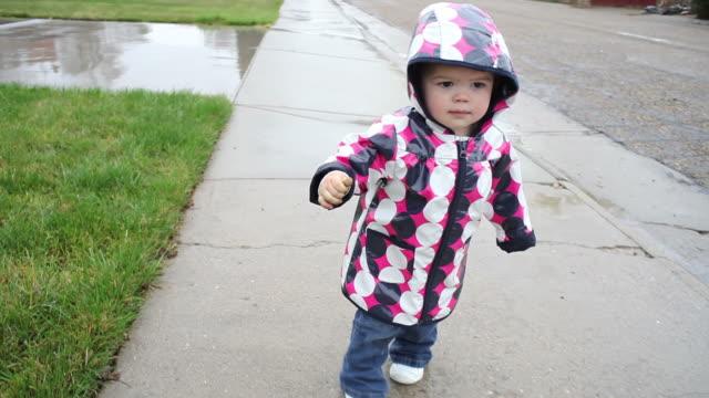 little girl walking along sidewalk in rain - endast flickor bildbanksvideor och videomaterial från bakom kulisserna