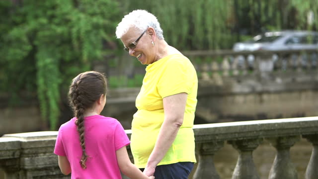 Little girl walking with grandmother in the park video