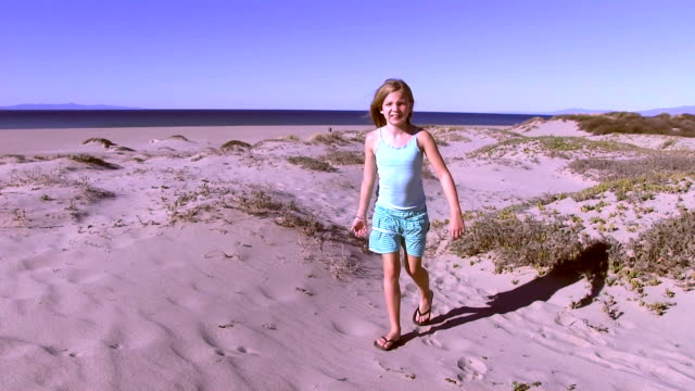 Little girl walks on sandy beach dunes video