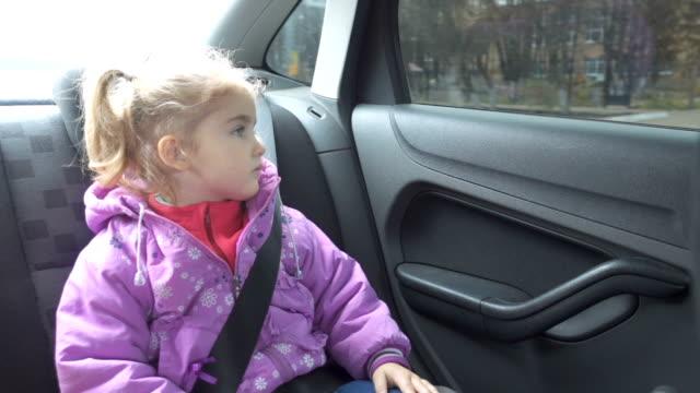vídeos y material grabado en eventos de stock de ropa de abrigo de niña mirando desde la ventana del coche. - niñas bebés