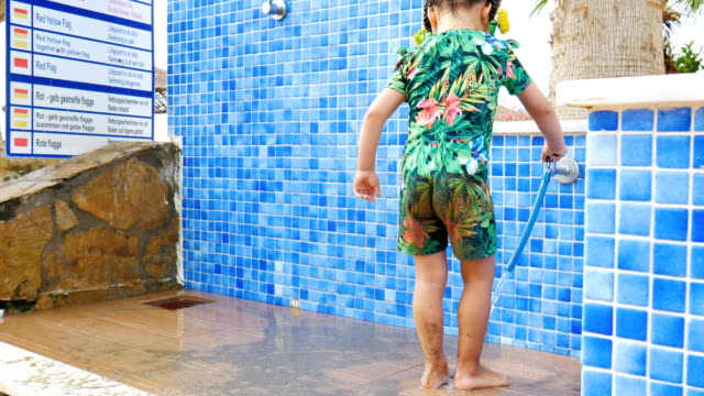 A little girl washes away the sand under a shower. A little cute beautiful girl washes away the beach sand under a shower. pigtails stock videos & royalty-free footage