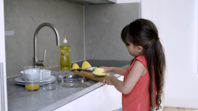 Little girl washing dish by herself
