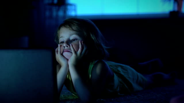 A little girl watches cartoons in the computer late in the evening. video