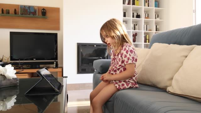 vídeos de stock e filmes b-roll de little girl watching tablet sitting on sofa - tv e familia e ecrã