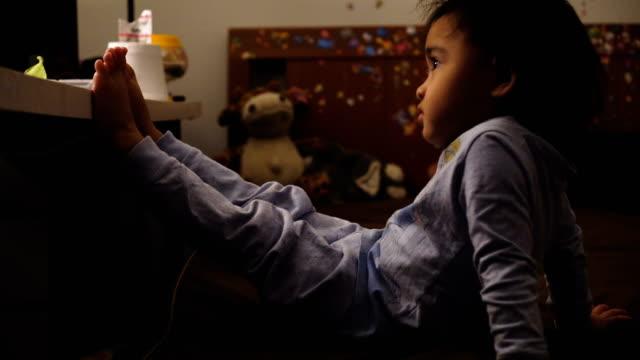 vídeos de stock e filmes b-roll de little girl watching television - tv e familia e ecrã