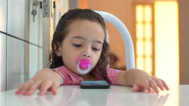 bambina che guarda il video sul cellulare - ciuccio video stock e b–roll