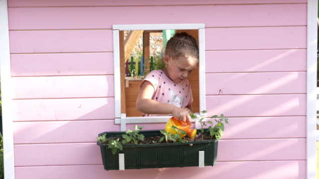 Little girl watering flowers in window box on pink playhouse. video