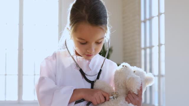 liten flicka bära medicinsk uniform holding stetoskop lyssnar leksak patient - förskoleelev bildbanksvideor och videomaterial från bakom kulisserna