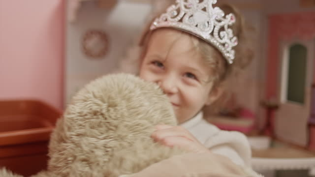 A little girl wearing a tiara hides her face behind a stuffed animal A little girl wearing a tiara hides her face behind a stuffed animal princess stock videos & royalty-free footage