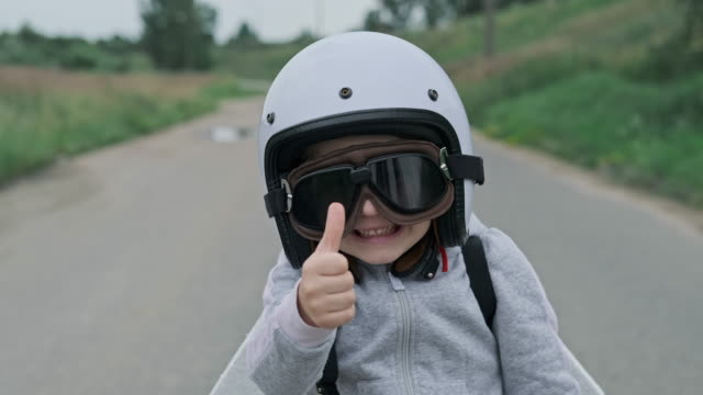 Little girl wearing protective glasses, helmet and thumbs up. 4K, UHD Little girl wearing protective glasses, helmet and thumbs up. Child putting on pilot glasses. Happy kid playing outdoors. Close up in 4K, UHD work helmet stock videos & royalty-free footage