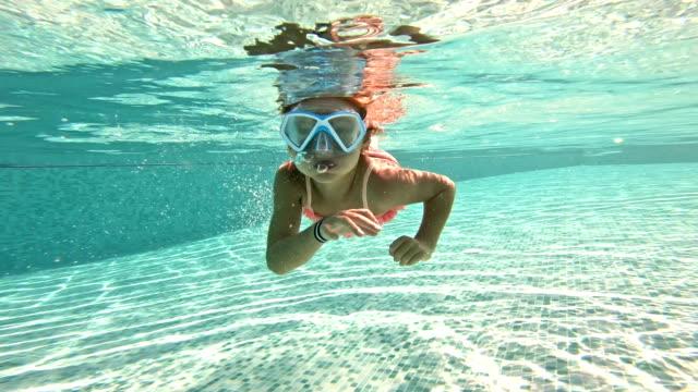 Little girl wearing snorkeling mask swimming underwater in the pool.