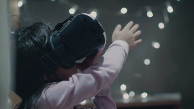 Little girl wearing virtual reality glasses A Baby Girl Wearing Virtual Reality Headset at Home robot stock videos & royalty-free footage