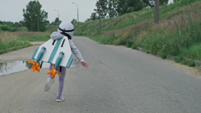 liten flicka bär vit hjälm, jetpack och kör på landsbygden väg som flygare - föreställningsförmåga bildbanksvideor och videomaterial från bakom kulisserna