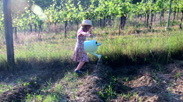 Petite fille porte la robe à fleurs et chapeau blanc. Petite fille des eaux du jardin - Vidéo