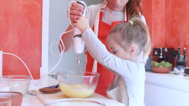 vidéos et rushes de petite fille, fouetter les oeufs avec la mère - batteur électrique