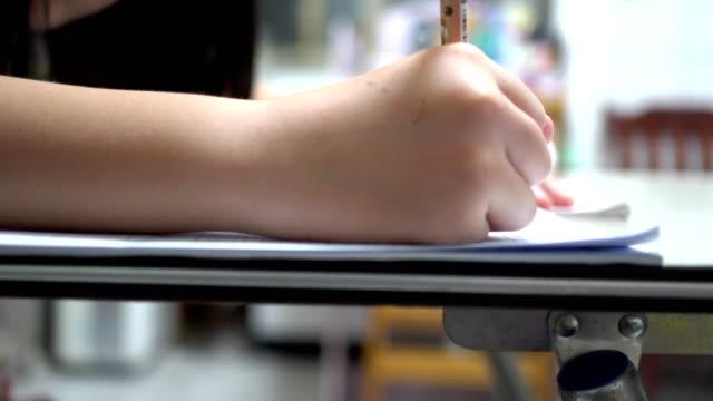 ragazzina che sta scrivendo i compiti. vista laterale. da vicino a portata di mano. - educazione primaria video stock e b–roll