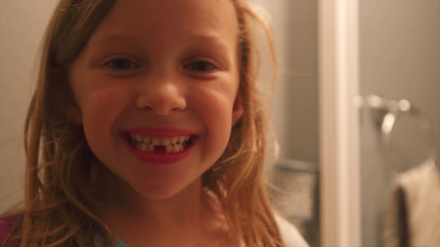A little girl who lost two teeth smiles at the camera, and makes a funny face in the mirror video