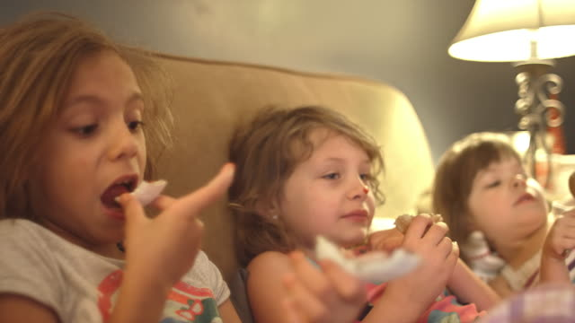 A little girl wipes jelly from a donut on her sister's face while they watch TV A little girl wipes jelly from a donut on her sister's face while they watch TV jello stock videos & royalty-free footage