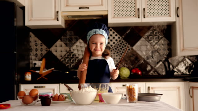 vídeos de stock e filmes b-roll de little girl with a rolling pin in her hands is preparing cupcakes in the kitchen - avental