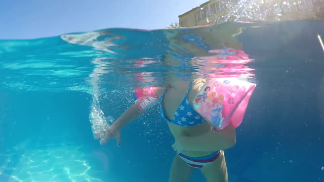 vídeos de stock e filmes b-roll de little girl with arm bands swimming floating in thermal spa pool water surface, half underwater view, slow motion - swim arms
