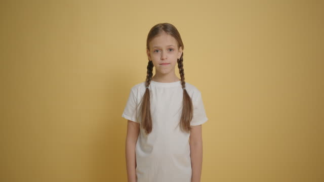 Little girl with braids smiling to the camera at yellow background slow motion Little girl with braids smiling to the camera at yellow background slow motion pigtails stock videos & royalty-free footage