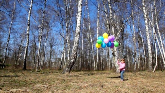 Little girl with bunch of balloons walks in spring forest video
