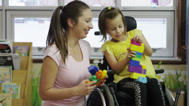 Little Girl with Cerebral Palsy A six year old girl with cerebral palsy at a daycare. disability stock videos & royalty-free footage
