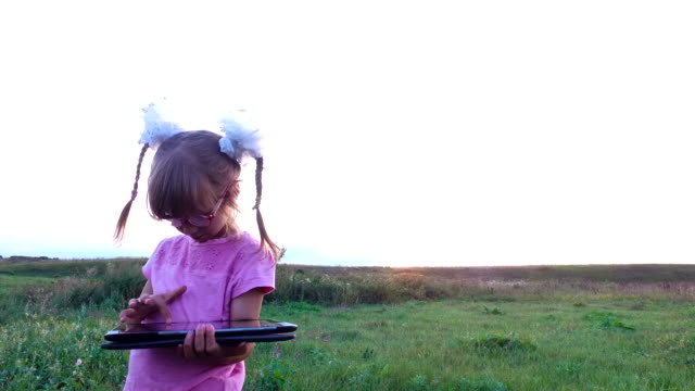 Little girl with enthusiasm plays on the tablet PC. Girl child with glasses stands on a green meadow. Little girl with enthusiasm plays on the tablet PC. Girl child with glasses stands on a green meadow. Summer evening at sunset. pigtails stock videos & royalty-free footage