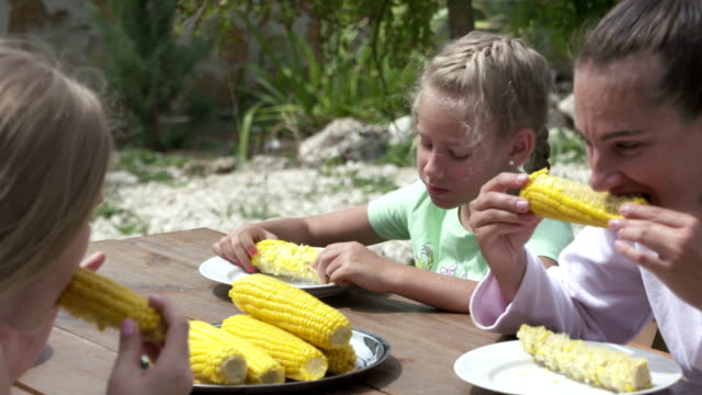 Little girl with friends enjoying lunch eating boiled sweet corn in backyard video