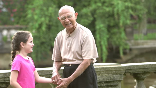 Little girl with great grandfather walking in park A 9 year old mixed race Hispanic and Caucasian girl walking with her great grandfather, an elderly Hispanic man in his 90s, in the park. They are holding hands, smiling. granddaughter stock videos & royalty-free footage