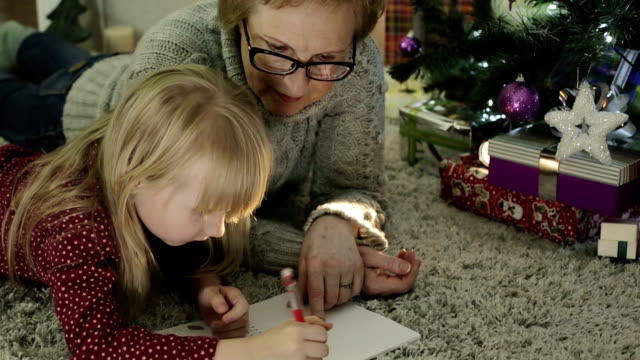 Little girl with her grandmother lying on the floor near a Christmas tree. video
