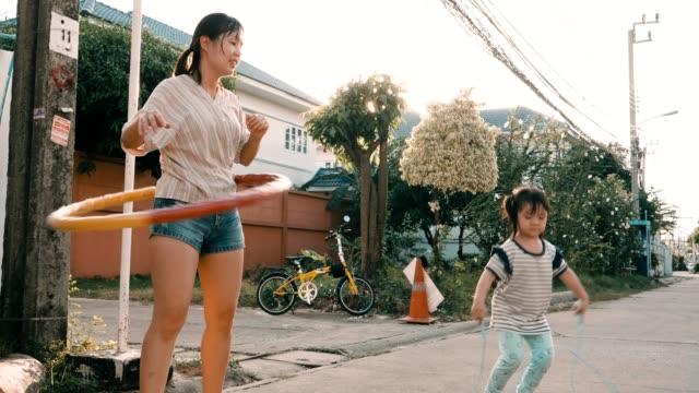 liten flicka med sin mamma hoppa rep och spela hula-hoop - tävlingsidrott bildbanksvideor och videomaterial från bakom kulisserna