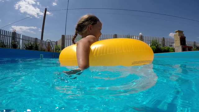liten flicka med uppblåsbar gummiring simmar i poolen - inflatable ring bildbanksvideor och videomaterial från bakom kulisserna