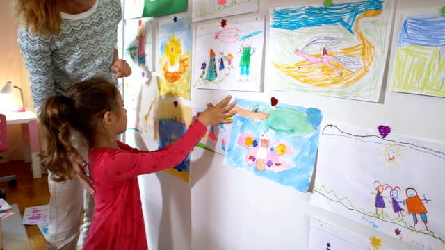 Little Girl with Mother Hang Children's Drawings on the Wall in Nursery