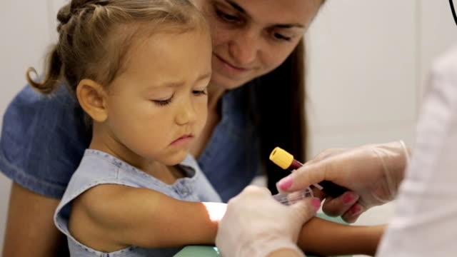 liten flicka med mamma på sjukhuset. sjuksköterska med flickans venöst blod för test - medicinskt stickprov bildbanksvideor och videomaterial från bakom kulisserna