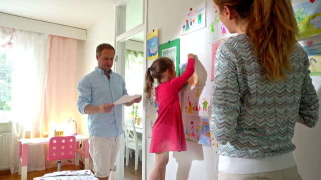 Little Girl with Parents Hang Children's Drawings on the Wall in Nursery