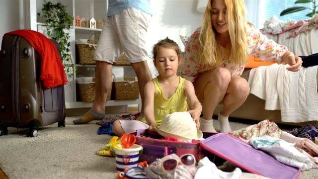 Little Girl with Parents Packing a Luggage for a Journey video